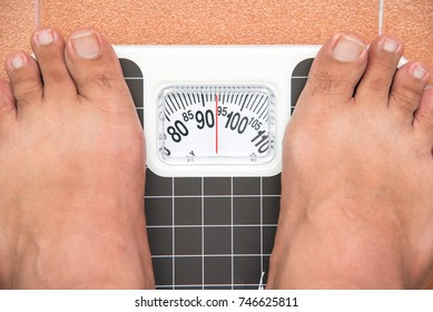 fat man on analog weight scale