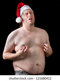 Fat man playing a naughty Santa Claus wearing his hat while being topless and grabbing his nipples making a funny face. What a interesting funny gift for a wife.