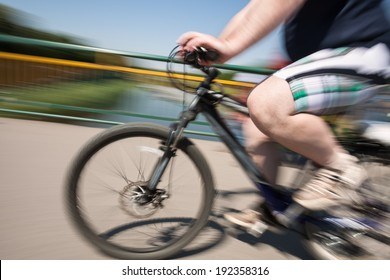Fat man rides a bicycle on city streets. Intentional motion blur