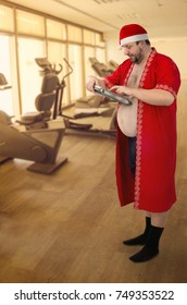 Fat man in Santa's costume looks closely at the scales standing in the gym. He has just weighed himself before working out. He wants to lose weight gained during Christmas holidays