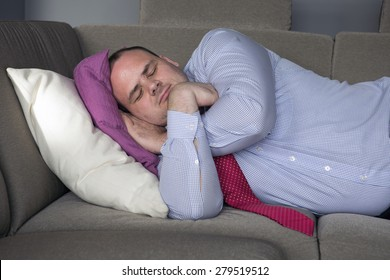 fat man in shirt and tie lying on couch and sleeps