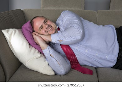 fat man in shirt and tie lying on couch and smiles