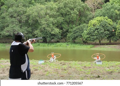 Fat Man Shooter is Skeet Shooting Clay Target (Pigeon) from House Machine Equipment at Riverside. Copy Space for Text.