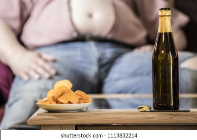 a fat man sits at a table on the beer and potato chips stand