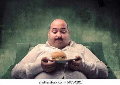 Fat man sitting on an armchair and looking at his hamburger