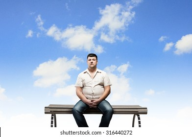 Fat man sitting on bench and looking away