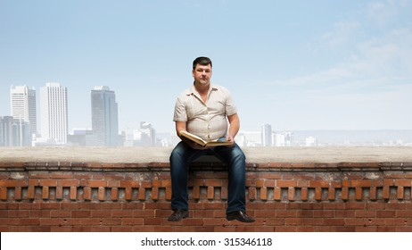 Fat man sitting on building top with book in hands