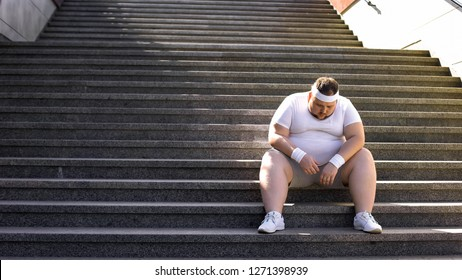 Fat man sitting on stairs after jogging, no faith in himself, insecurities