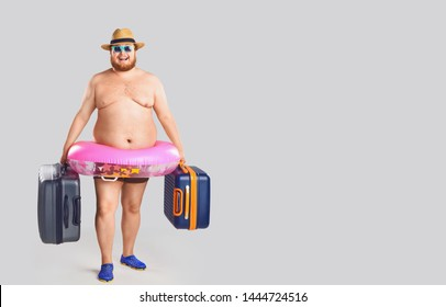 A fat man in a swimsuit with suitcases and a rubber ring against