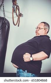Fat man trains box in gym
