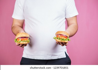 fat man with two tasty burgers. fast food and weight gain, gluttony, hunger, unhealthy eating