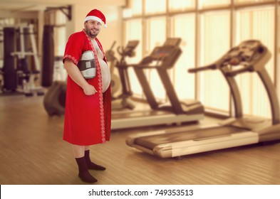 Fat man wearing Santa suit holds scales. He gained overweight during Christmas vacation and intend to lose it in the gym. Blurred indoor background