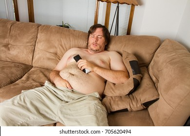 Fat obese man asleep on the couch with remote in one hand and the other hand shoved down the front of his pants. Shows obesity due to lack of excercise.