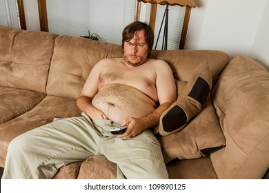 Fat obese man  on the couch with remote in one hand and the other hand shoved down the front of his pants. Shows obesity due to lack of exercise.