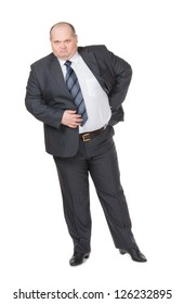 Fat overweight businessman in a stylish suit standing with his hand on his hip glowering at the camera with a displeased expression, studio portrait on white