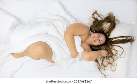 Fat plump woman with dark long hair, beaming with joy, view from above, copy space