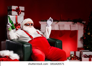 Fat santa claus sit chair hold beer bottle house concept with x-mas decoration gift box wear suspenders isolated bright shine color background