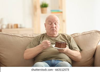 Fat senior man eating cake while sitting on sofa at home. Weight loss concept