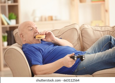 Fat senior man playing videogame and eating hamburger while lying on sofa at home. Sedentary lifestyle concept