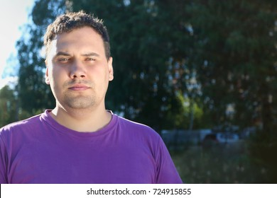 Fat serious man in t-shirt poses outdoor in sunlight at summer day
