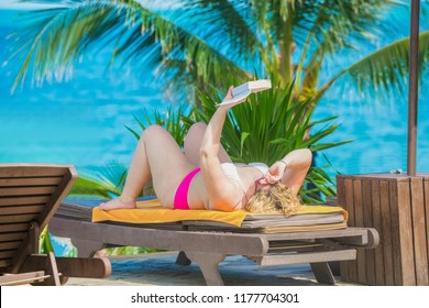 Fat  tourist woman in pink bikini lying down on sun loungers by the sea with turquoise sea background.28 June 2018  Koh Samui Surat Thani Thailand