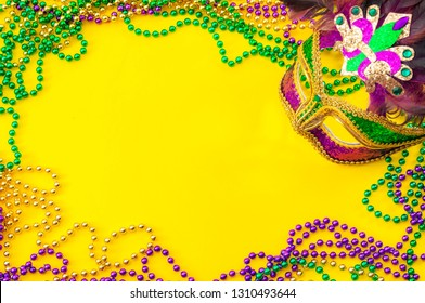 Fat Tuesday and Mardi Gras carnival concept theme with close up on a face mask full of color, feathers and texture and golden, green and purple beads isolated on yellow background with copy space