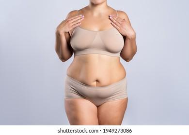 Fat woman in beige underwear on gray background, overweight female body, studio shot