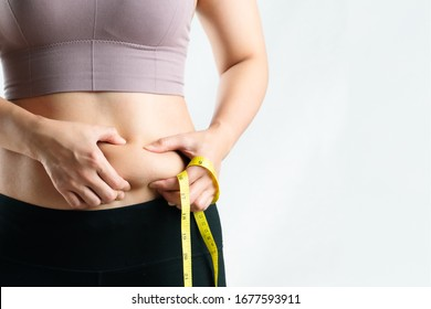 fat woman, fat belly, chubby, obese woman hand holding excessive belly fat with measure tape, woman diet lifestyle concept