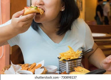 fat woman bite piece of pizza,overweight female is eating fast foods,asian girl is hungry