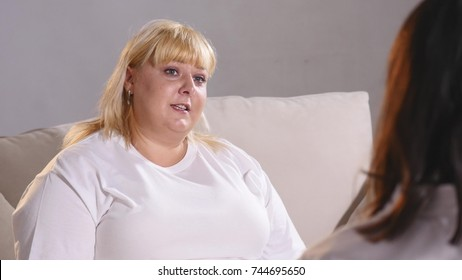 a fat woman complains to a dietician about her figure. Fat woman crying