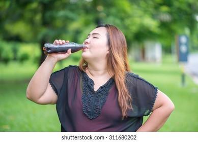 Fat woman drink cola in garden