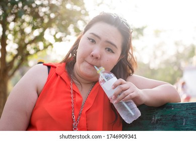 fat woman drink water in the green park