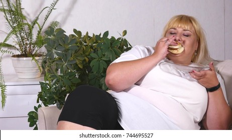 fat woman eating a burger, watching TV and laughes