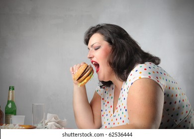 Fat woman eating a hamburger for dinner