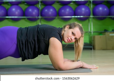 Fat woman is engaged in pilates in a fitness gym. A girl with a lot of overweight trying to lose weight with the help of yoga, stands in the bar on her forearms. Side view.