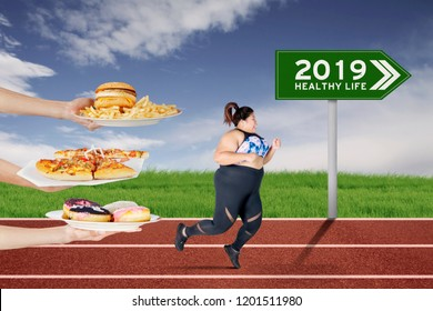 Fat woman escapes from unhealthy foods offered while running on the track with text of 2019 healthy life on the green signpost