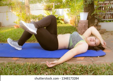 fat woman exercise tired give up lying down on yoga mat outdoor at home over obese belly bored tired face background