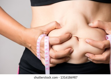 Fat woman hand holding excessive belly fat with measuring tape. Healthcare and woman diet lifestyle concept to reduce belly and shape up healthy stomach muscle.