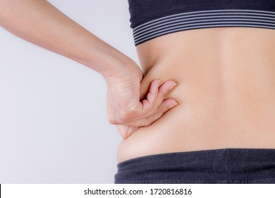 Fat woman hand holding excessive belly fat. Healthcare and woman diet lifestyle concept to reduce belly and shape up healthy stomach muscle.