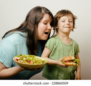 fat woman holding salad and little cute boy with hamburger teasing isolated