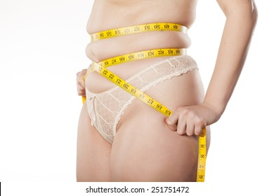 fat woman measure her waist with measuring tape