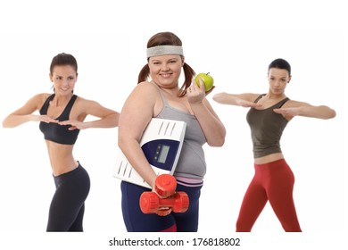 Fat woman on diet doing fitness exercise with slim sporty girls.