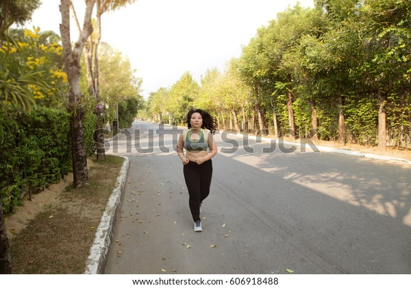 Fat woman running exercise smile face in park weight loss concept