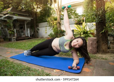 Fat woman side plank with rotation dumbbell abs muscle exercise weight loss concept