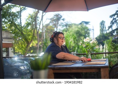 Fat woman sit in cafe alone, drink and eat on coffee break time