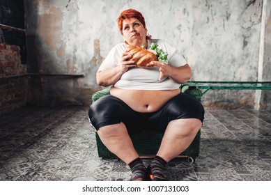 Fat woman sits in chair and eats sandwich, bulimic