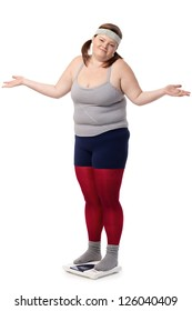 Fat woman standing on scale disappointed with opened arms, wearing sportswear.