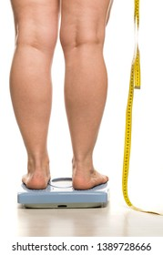 a fat woman stands on a scales and holds a measuring tape on white background