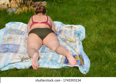 fat woman sunbathes on grass. An aged woman lies on a plaid under the sun. Retired woman in a swimsuit.