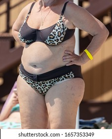 Fat woman in a swimsuit near the pool. Holiday at the resort